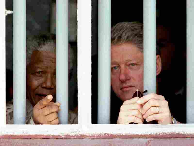 President Bill Clinton and Mandela peer through the bars of prison cell No. 5 on March 27, 1998. Mandela was jailed for 18 years in the cramped gray cell in his struggle against apartheid.