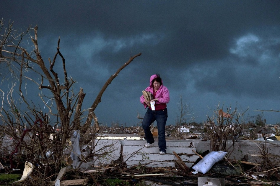 "Janet Martin attempts to salvage items from her brother's home in Joplin. ""Twenty minutes before the storm, he left to go to church.  He would have been in that basement if he hadn't gone,"" Martin said.  (Getty Images)"