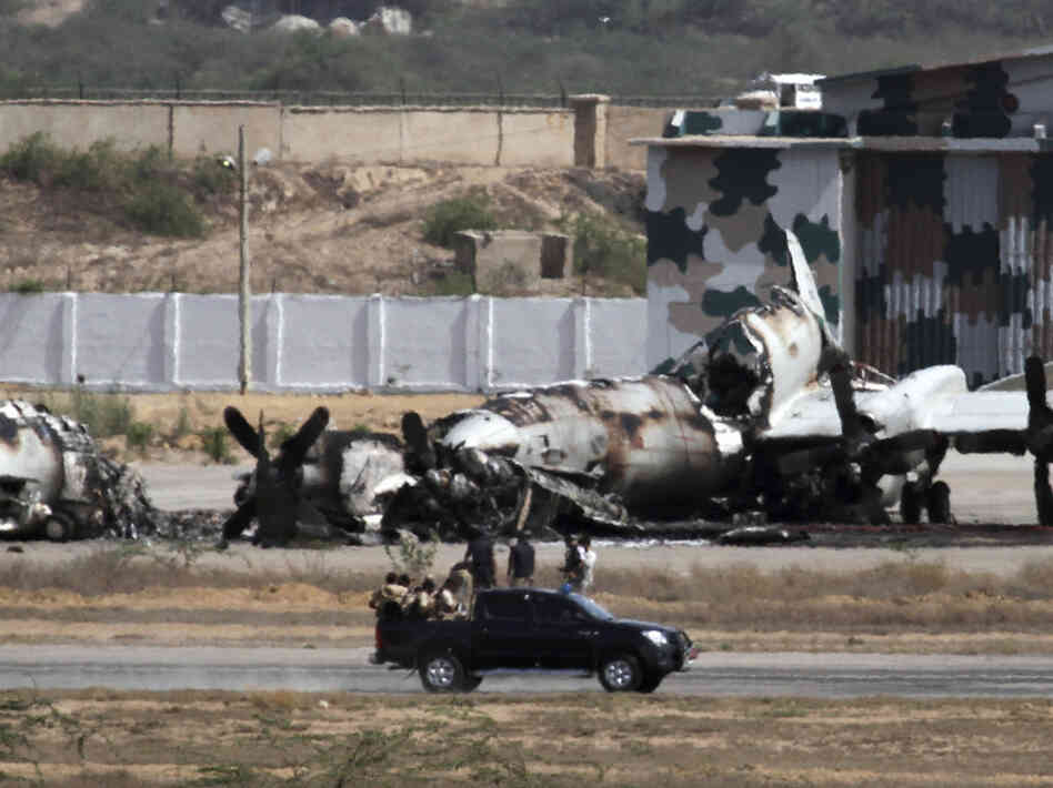 Pakistani troops gather next to a burned plane inside a naval base following an attack by militants in Karachi, Pakistan, on Monday.