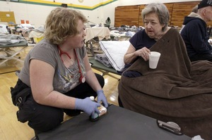 Delma Boyd of Joplin, Mo., (right) talks with medical technician Angela O'Leary of Purdy, Mo., in a temporary American Red Cross shelter at Missouri Southern State University in Joplin.
