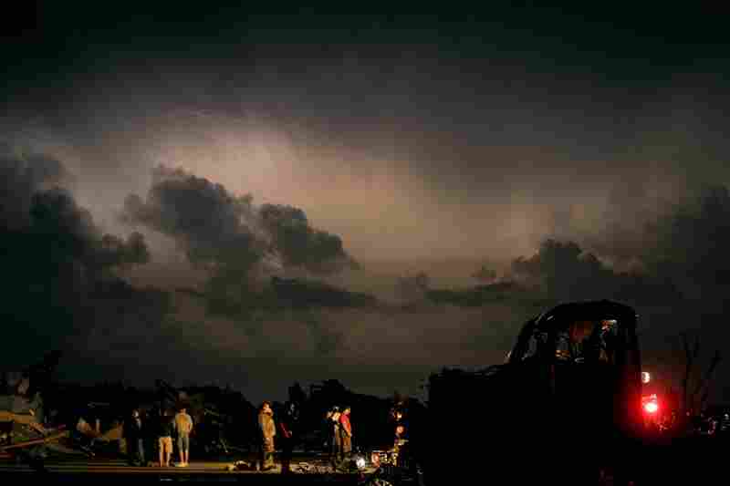 Emergency workers wait for a medical team after finding a body in a tornado-ravaged car. A twister tore through nearly six miles of the city Sunday.