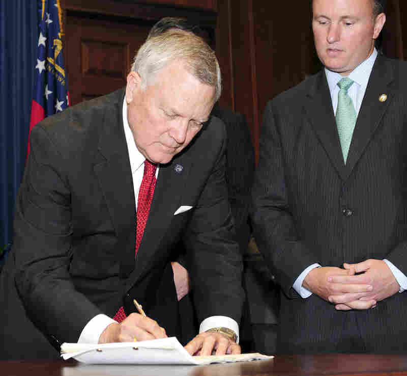 Georgia Gov. Nathan Deal signs the state's new immigration bill in Atlanta May 13 as state Rep. Matt Ramsey — the bill's sponsor — looks on.