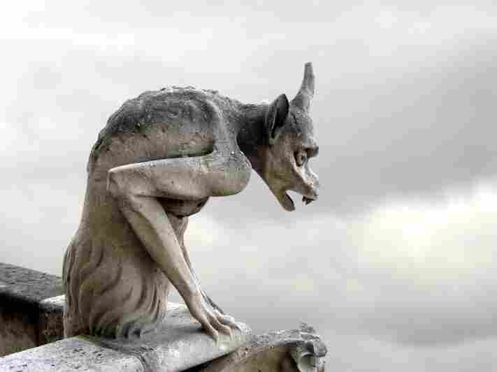 A creepy gargoyle looks onto an overcast sky.