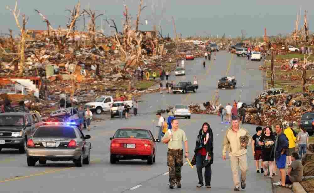 Residents of Joplin, Mo., walk west on 26th Street near Maiden Lane after a tornado hit the southwest Missouri city Sunday evening.
