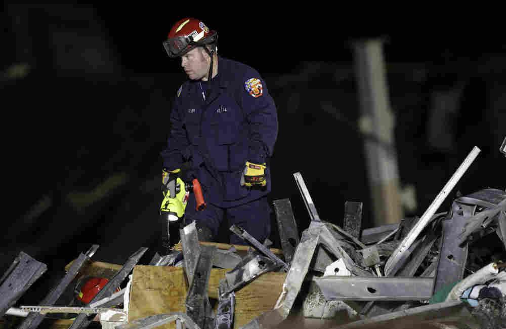 An emergency worker searches a Walmart store severely damaged by a tornado in Joplin, Mo.