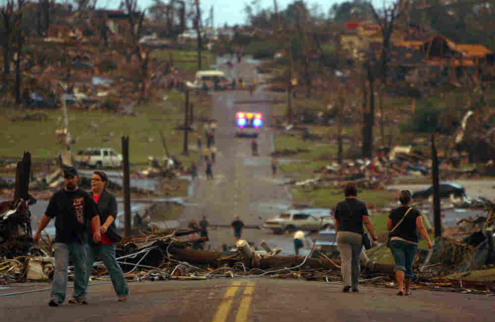 People walk down a joplin street littered with destroyed for Home builders in joplin mo