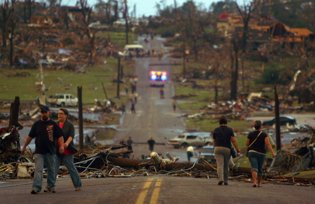 People walk down a Joplin street littered with destroyed trees and homes in Joplin, Mo., on Sunday, May 22, 2011.