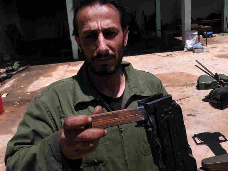 """At the rebels' outdoor machine shop, they rehabilitate antique automatic weapons and sometimes redesign them.  Saleh Likhfayfe shows off the new """"grip"""" welded onto a salvaged machine gun."""