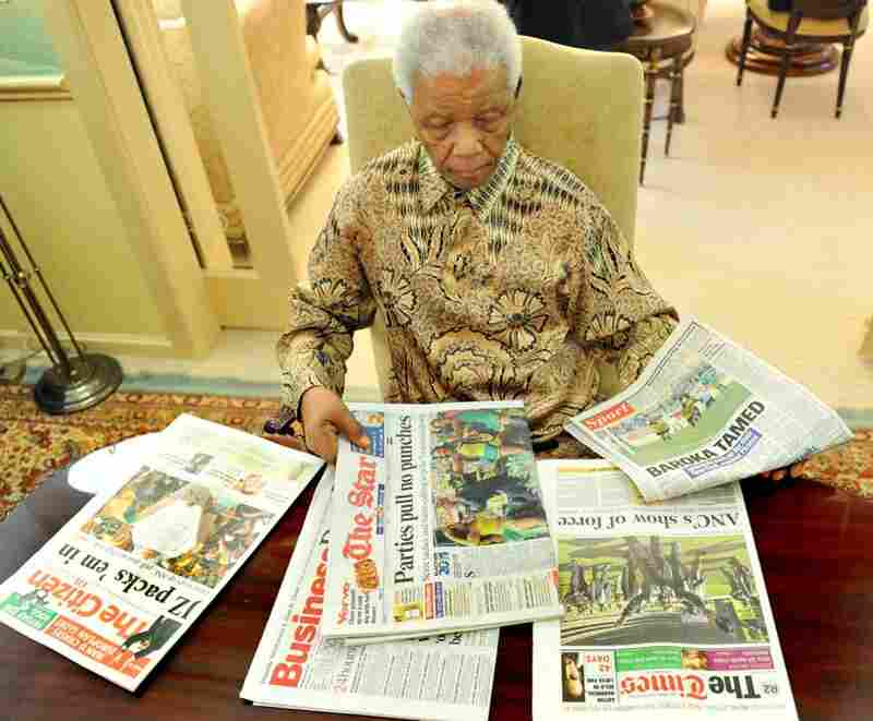 Mandela shifts through newspapers after casting his vote for local elections on May 16, 2011 at his home in Johannesburg.