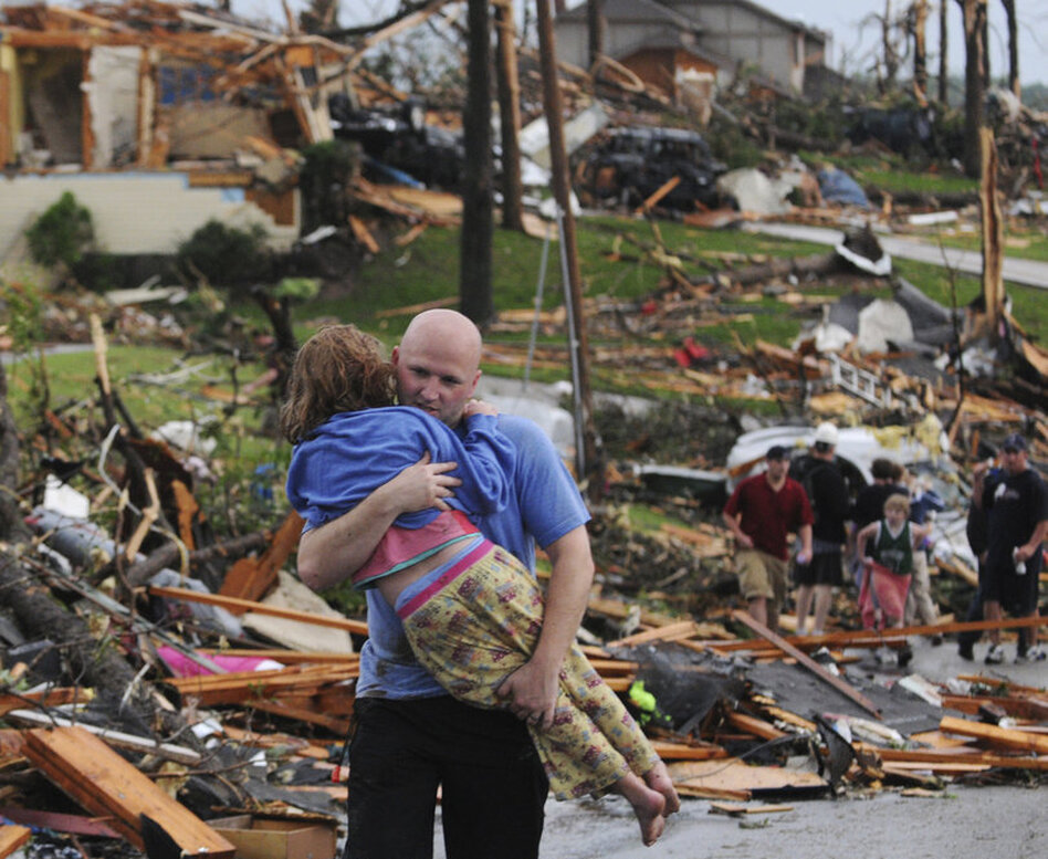 A man carries a young girl who was rescued after being trapped with her mother in their home after a tornado hit Joplin.  (AP)