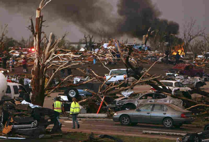 Emergency personnel walk through a neighborhood severely damaged by a tornado near St. John's Regional Medical Center.