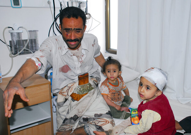 A father and his daughters sit on a hospital bed after their house was hit as fighting rages in the al-Hasaba neighborhood, north of the capital Sanaa on May 24, 2011.