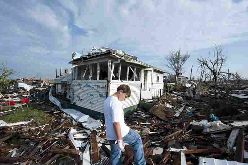 Tucker Scott looks for his pet cat in the rubble of the home where he lived with his mother.