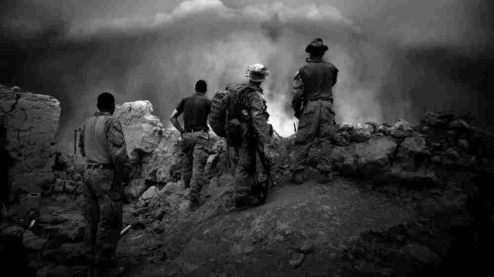 Members of the Bravo Company, 1st Battalion, 5th Marine Regiment watch as a massive dust storm is just seconds away from enveloping Patrol Base Fires in Sangin District, Helmand province, southern Afghanistan. Roughly 100,000 service members are in Afghanistan, and their future there is being newly considered in Washington after the death of Osama bin Laden in Pakistan.