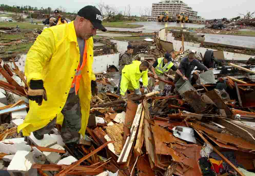 Tom Cravens of the Pryor, Okla., Police Department searches the rubble of a home near the now closed St. John's Regional Medical Center in Joplin, Mo., on Monday, May 23, 2011.