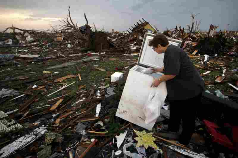 Anita Stokes salvages meat from a freezer where her home once stood in Joplin.