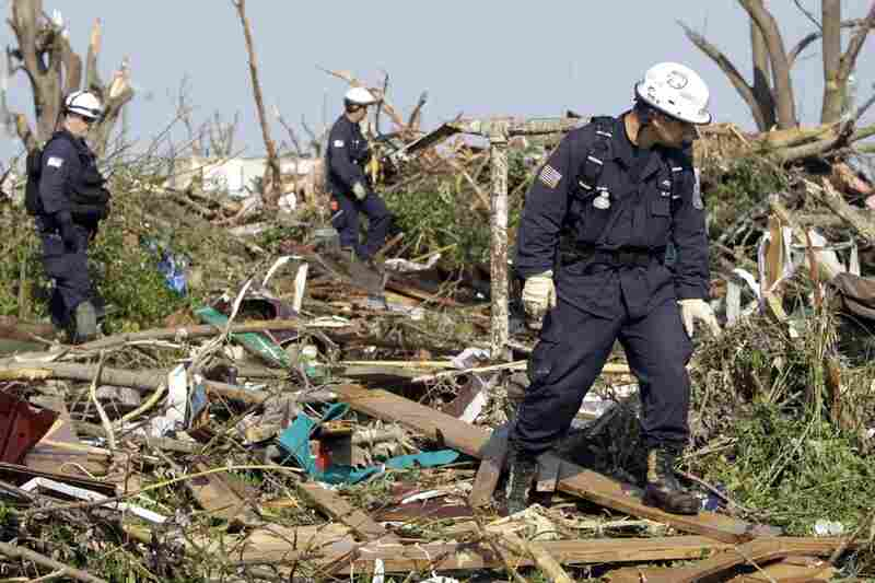 Oklahoma Task Force One search-and-rescue members, from left, Jim Winham, Nick Swainston and Kevin Mann search through debris for victims.