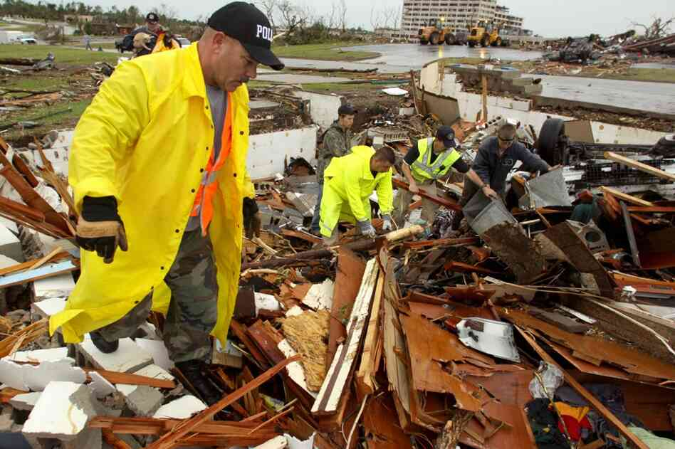 Tom Cravens of the Pryor, Okla., Police Department looks through the rubble of a destroyed home near the St. John's Regional Medical Center in Joplin, Mo.