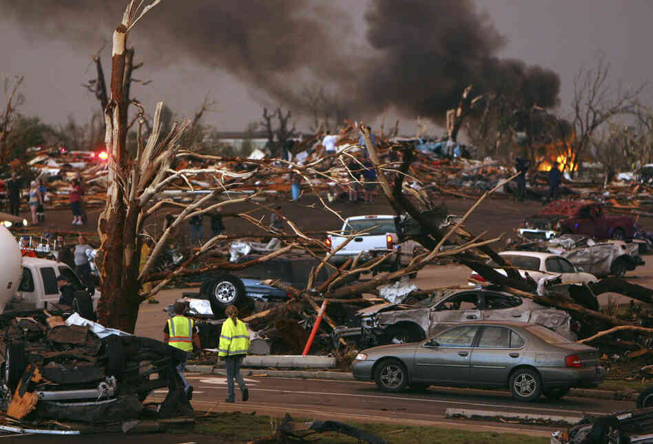 Emergency personnel walk through a neighborhood severely damaged by a tornado near St. John's Regional Medical Center.