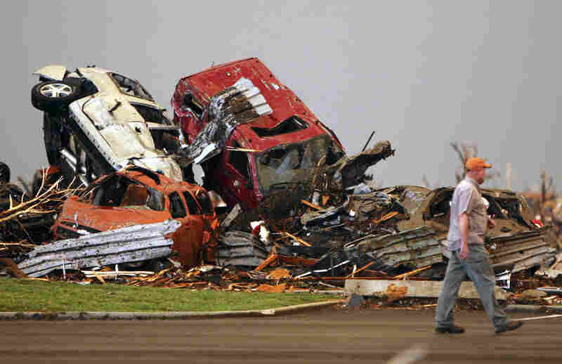 A man walks past destroyed vehicles in the parking lot of St. John's Regional Medical Center.