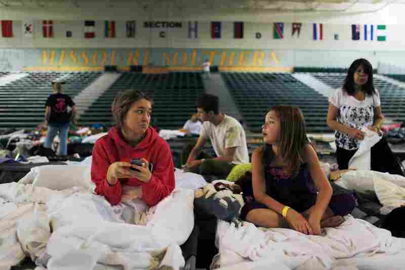 Breanna Hoosier (left) and her sister, Becca, sit on their cots in the Red Cross shelter set up at Missouri Southern State College.