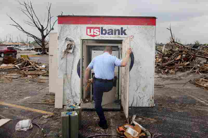 Armored car courier Josh Beck works on salvaging cash from an ATM that was damaged and tossed some 20 feet.