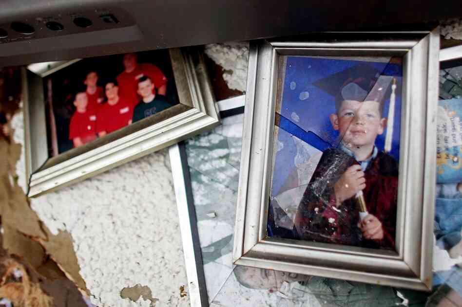 Damaged photos lie among debris in Joplin, Mo.