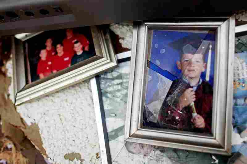 Damaged photos lie among debris in Joplin, Mo.