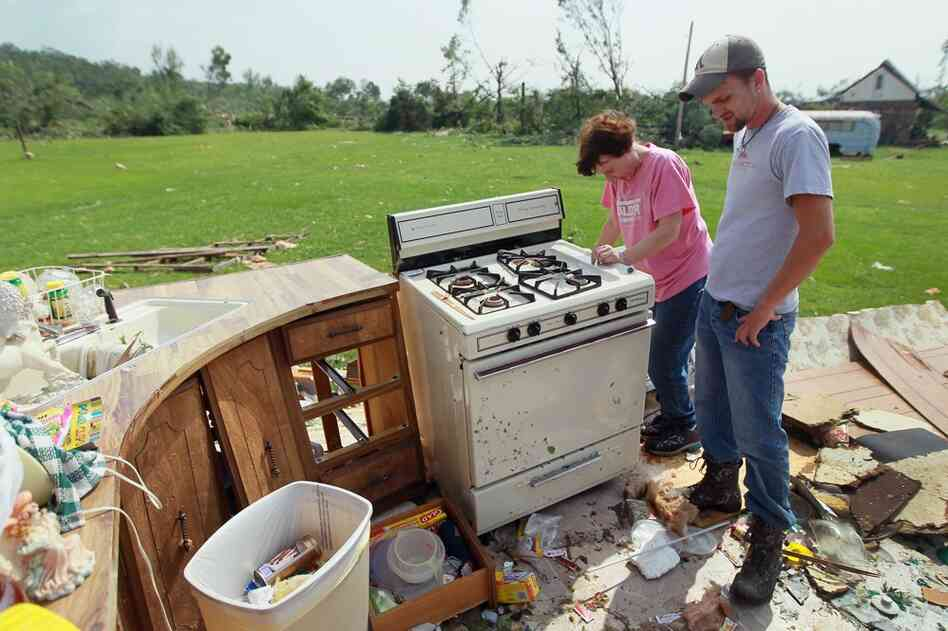 Elizabeth Vandenberg  and Paul Garnec stand in what remains of her living room as she salvages what she can from her trailer in Denning, Ark.