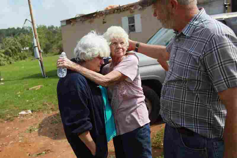 Kathy McCormick (left), Alice Vandenberg and William Schaffer console each other as they deal with the loss of their families homes Denning, Ark.