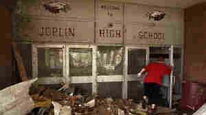 A woman makes her way into the damaged main entrance of Joplin High School in Joplin, Mo., Tuesday, May 24, 2011.