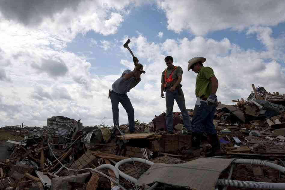 Darren Braker uses an axe to break through the floor of a doctor's office with the aid of Jesse Braker (center) and Brent Luthi on Wednesday in Joplin, Mo. The men were attempting to help a local family physician retrieve patient records from a basement office.