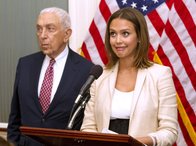 Actor Jessica Alba, accompanied by Sen. Frank Lautenberg (D-NJ), reacts when a buzzer calling for a vote goes off during a n