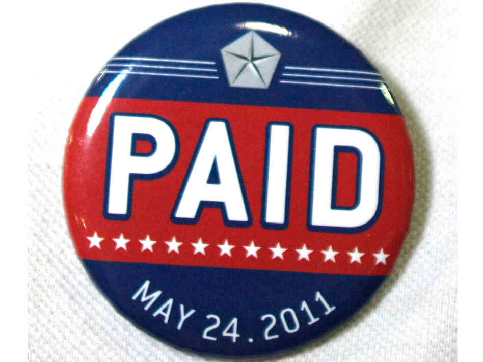 "An assembly line worker wears a pin labled ""PAID"" on his shirt before Chrysler Grou"
