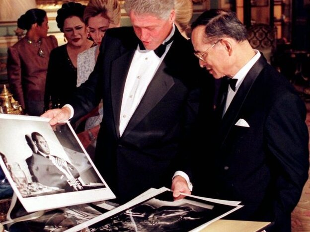 President Clinton shows Thai King Bhumibol Adulyadej photos of famous American jazz musicians as they exchange gifts at Bangkok's Grand Palace on Nov. 26, 1996.