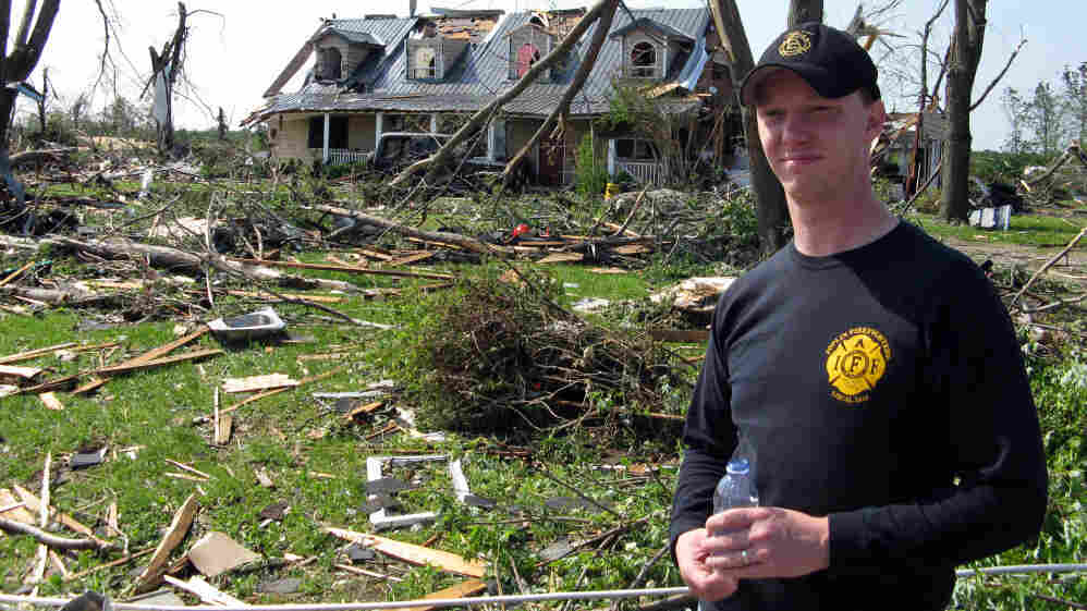 "Brad Eichelberger, a Joplin firefighter and a friend of Thomas Herrod, stands outside his wrecked home in Joplin, Mo. ""I'm all right. I'm relatively unhurt. We can rebuild all this,"" he says."