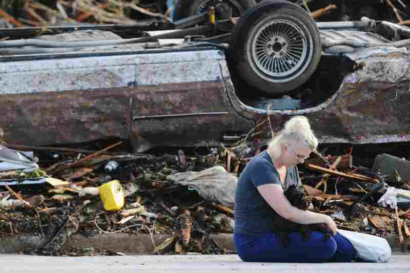 Heidi Ackerson sits in the street near her home in Joplin. Ackerson and her husband hid in a closet during the tornado.