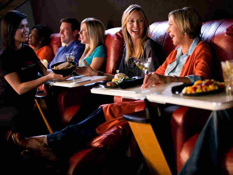 Viewers dine in at an AMC theater. Tickets to movies that offer this option cost between $9 and $15, depending on time and date of showing.