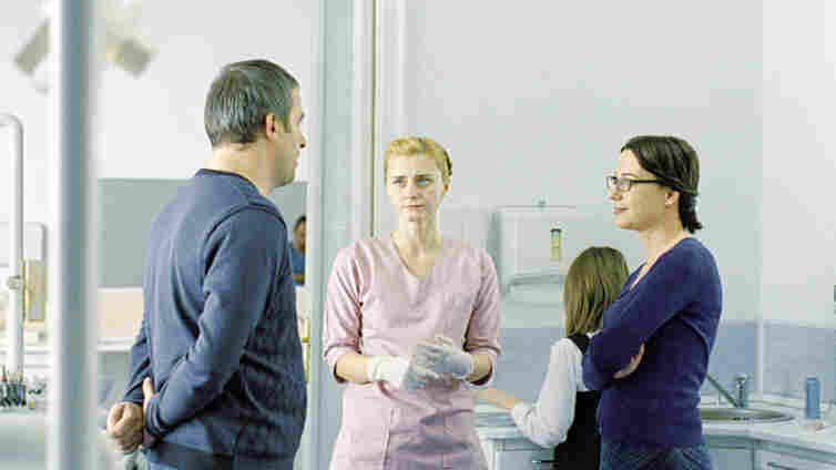 A Love Triangle, With Sharp Edges: Paul (Mimi Branescu, left) is an affable guy who loves his wife — and their daughter's orthodontist (Maria Popistasu, middle), too. Lover and wife (Mirela Oprisor, right) meet during a dentist appointment that thrums with tension and shame.
