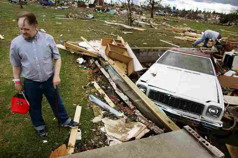 Steve Goebel (left) stands outside the crawlspace of his destroyed home after a massive tornado passed through Duquesne, Mo. Gobel was trapped for hours after cars were blown over the crawlspace.