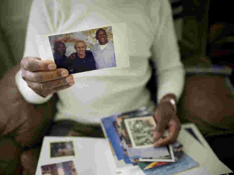 Robert Dixon Sr. holds a photograph of his son, Robert Dixon Jr. (far right), his son's mentor Bob Stuart, and himself (far left).