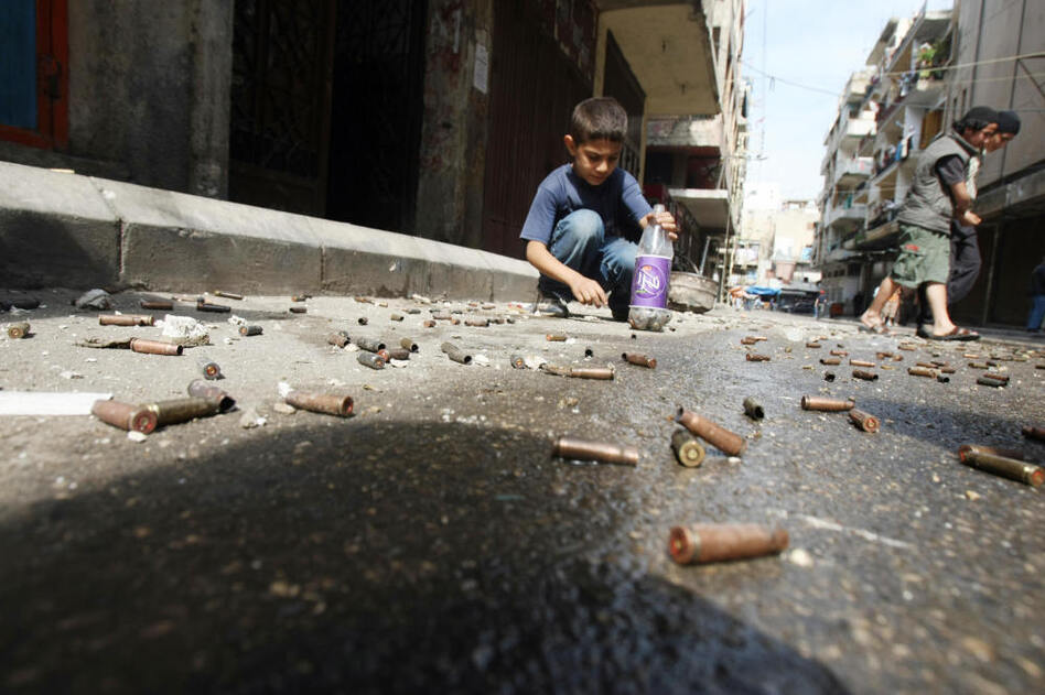 Children collect bullet casings at the scene of overnight fighting between Sunnis and Alawites in Tripoli on May 11, 2008.