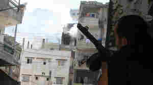 Smoke billows from the Jabal Mohsen community while a Sunni gunman takes cover behind a wall in the Bab al-Tabbaneh neighborhood during clashes in Tripoli, Lebanon, on July 9, 2008.