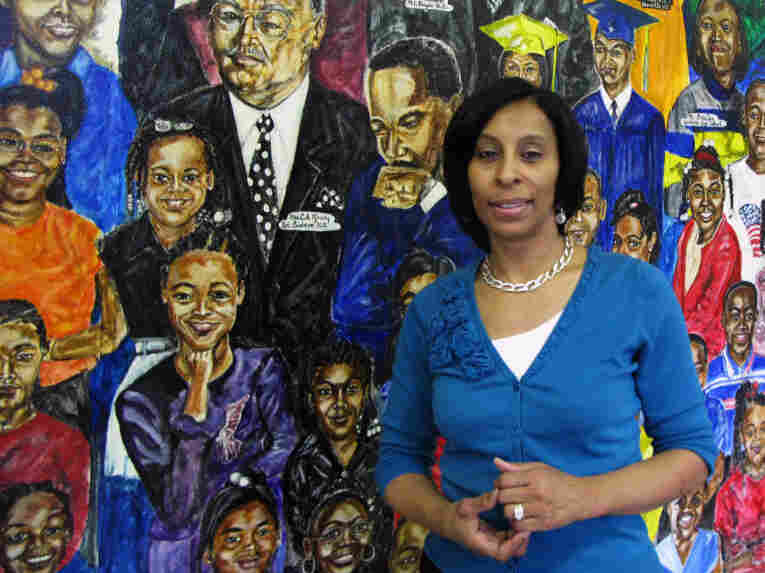 Janice Richardson, principal of Carstens Elementary School, stands in front of a  mural in the school's entryway. The Detroit Public School system is losing thousands of students, and Carstens  may have to close or become a charter.