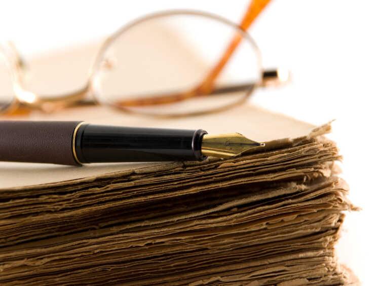 Glasses and a pen rest on a manuscript.
