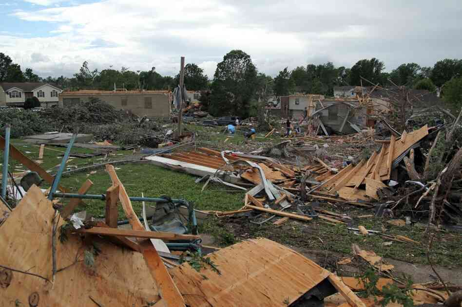 People pick through the debris in the wreckage of homes damaged by a tornado in Sedalia, Mo., on