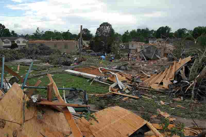 People pick through the debris in the wreckage of homes damaged by a tornado in Sedalia, Mo., on Wednesday.