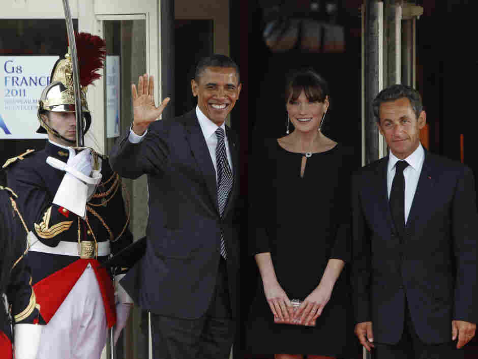French President Nicolas Sarkozy, right, and his wife Carla Bruni-Sarkozy, center, welcome US President Barack Obama to Le Ciro's Restaurant, during a dinner meeting for the G8 summit in Deauville, France.