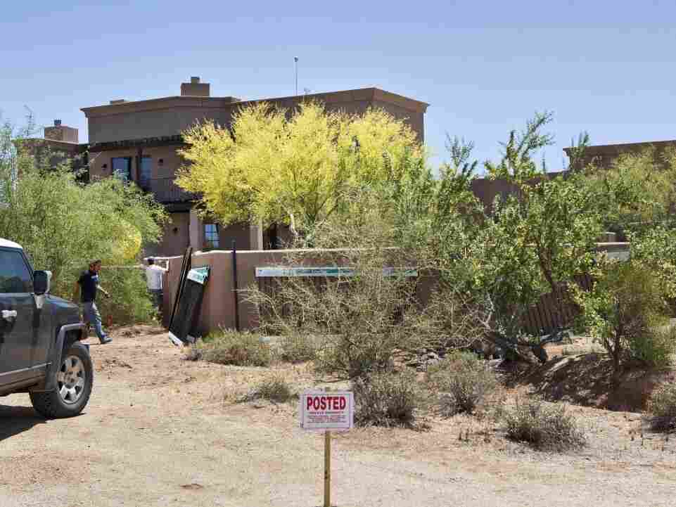 Workers install a fence around a home Monday, May 23, 2011 in Scottsdale, AZ whose purchase spurred speculation Sarah Palin was the purchaser.