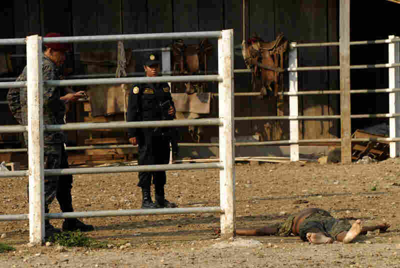Investigators work at the site of a massacre at a ranch in northern Guatemala. Most of the 27 people killed were decapitated.